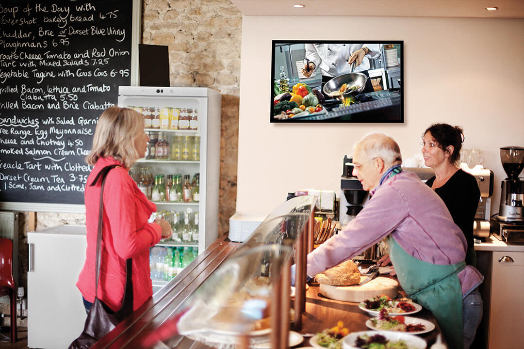 woman ordering at bakery with flatscreen tv on wall
