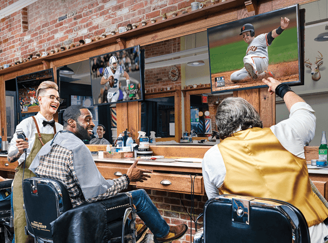 Barber cutting mans hair while watching TV at a barber shop